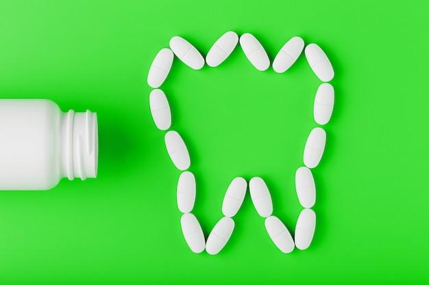 Calciumvitamine in de vorm van een tand die uit een witte pot op een green is gemorst.
