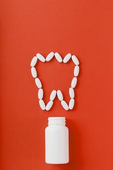 Calciumvitamine in de vorm van een tand die uit een witte pot op een rood is gemorst.