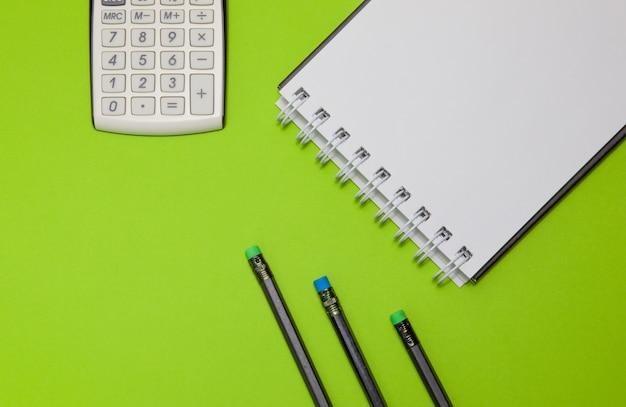 Calculator, blocnote en zwarte potloden op een groene achtergrond.