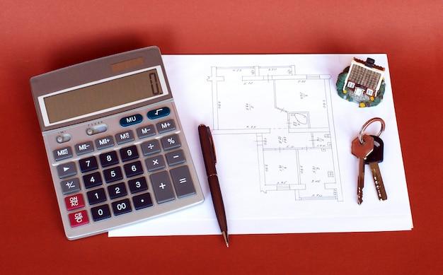 Calculator en pen voor een model van het villahuis met een blauwdruk.