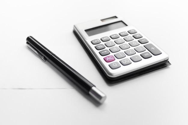 Calculator met een pen en document nota met geïsoleerd schuldwoord
