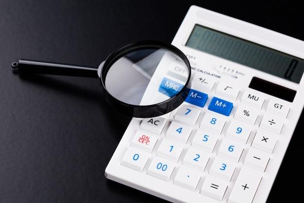 Calculator met een vergrootglas op een zwart oppervlak
