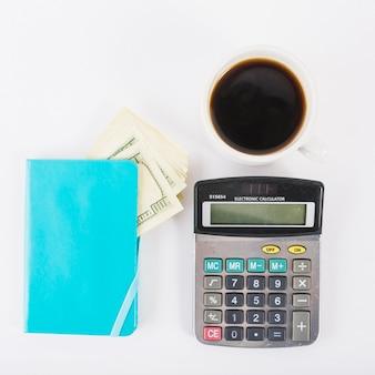 Calculator met geld in notitieblok op tafel