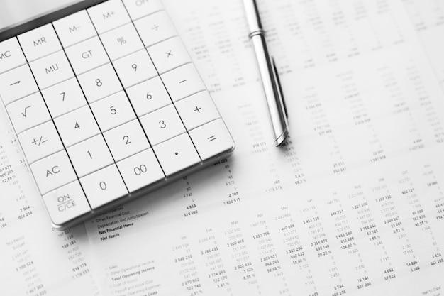 Calculator met pen op financiële gegevens. bedrijfs- en financieel onderzoeksconcept.