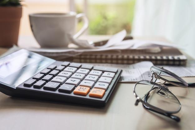 Calculator met rekeningen, belastingen, bankrekeningsaldo en het berekenen van huisonkosten