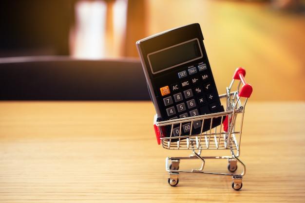 Calculator met shopingkar op houten lijst in het bedrijfs online concept van het webnetwerk