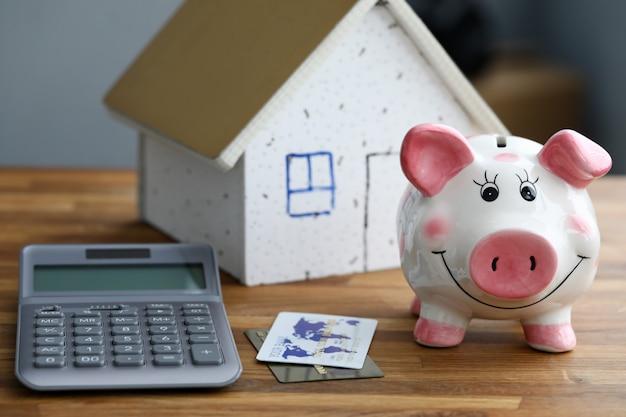 Calculator met spaarvarken met huis