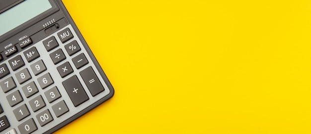 Calculator op een uitgerekt gele ruimte, bedrijfs en financiënconcept
