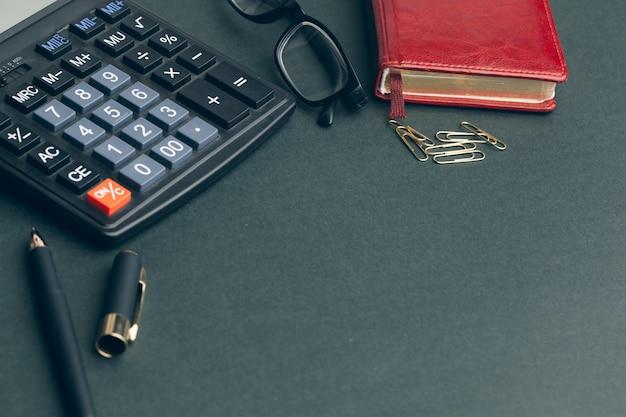 Calculator op lijst in bureau, zwarte copyspaceachtergrond