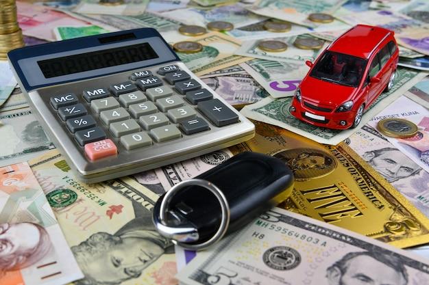 Calculator, sleutels en rode speelgoedauto op een verscheidenheid van nationale bankbiljetten. van de kosten van aanschaf, huur en onderhoud van een auto.