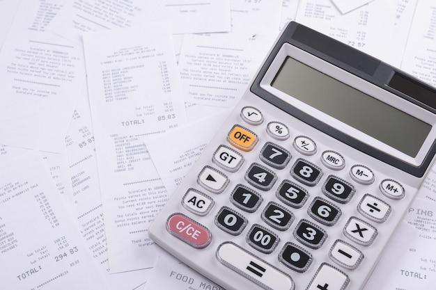 Calculator voor het tellen van een stapel cheques van aankopen in de winkel op een houten achtergrond. bovenaanzicht. plaats voor tekst. kopieer de ruimte.