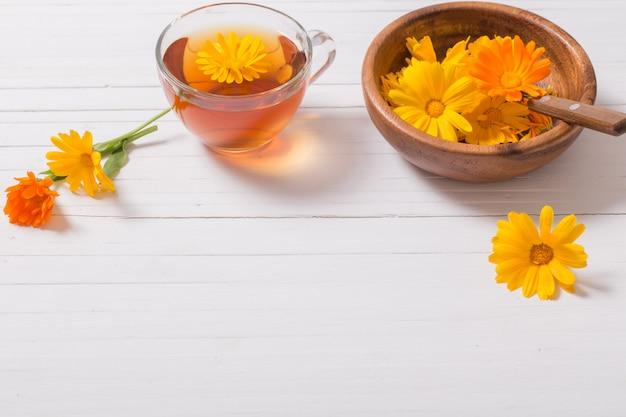 Calendula (goudsbloem) kruidenthee op witte houten tafel