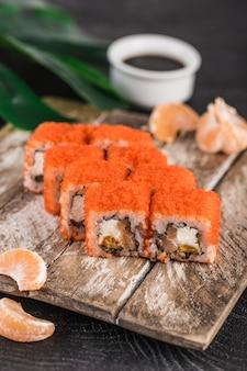 California roll met rode kaviaar, zalm en mandarijnen in roomkaas op een donkere ondergrond