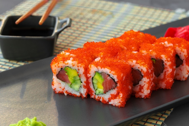 California sushi roll geserveerd op zwarte keramische plaat close-up