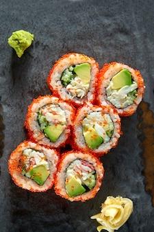 California sushibroodje met krab, avocado, komkommer en tobiko kaviaar geserveerd op een bord met wasabi en gember. isolatie op een zwarte tafel. japans eten