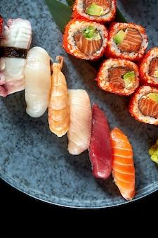 Californisch sushirolletje met zalm in tobiko kaviaar en diverse sushi. sushi met zalm, tonijn, garnalen