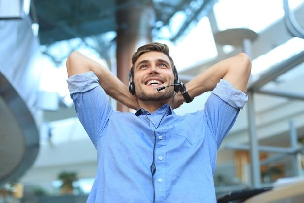 Call center operator in headset rust op de werkplek op kantoor.