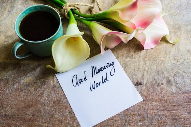 Calla bloemen en kop og koffie op rustieke lijst