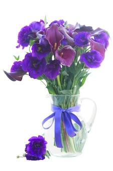 Calla lelie en eustoma bloemen in glazen vaas op wit wordt geïsoleerd