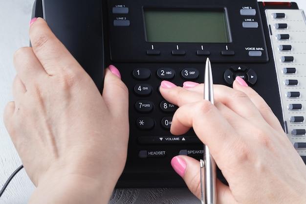 Callcenter of kantoortelefoonconcept, vrouwelijk vingerpersnummer op phonepad