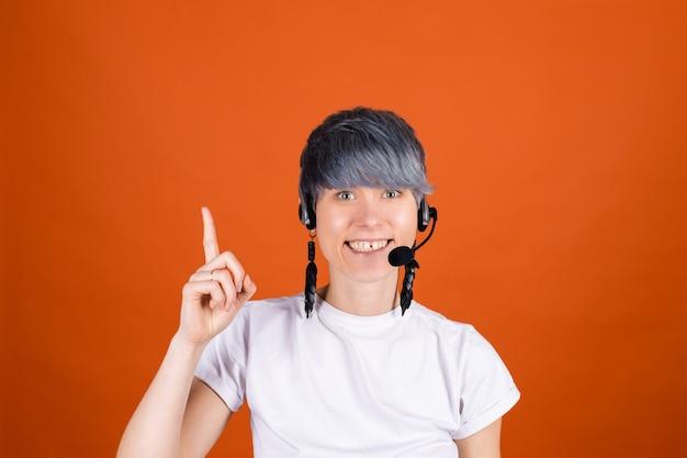 Callcenterassistent met koptelefoon op oranje muur ziet er gelukkig en positief uit met zelfverzekerde glimlachpuntvinger omhoog