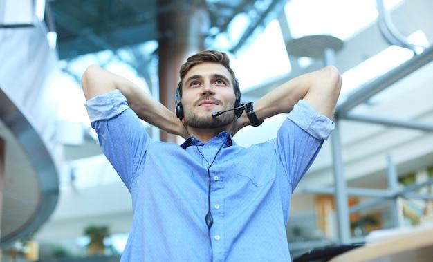Callcentermedewerker in headset die op de werkplek op kantoor rust