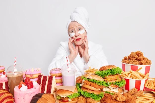 Calorieën en ongezond voedingsconcept. verrast gerimpelde oude vrouw houdt haar handen op het gezicht terwijl ze onder de indruk is van