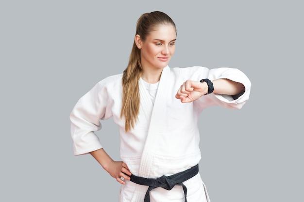 Calorieën verbranden. atletische tevreden jonge blonde vrouw die naar een slim horloge kijkt dat verbrande calorieën telt tijdens de training, met behulp van fitnessarmband. indoor studio-opname, geïsoleerd op een grijze achtergrond
