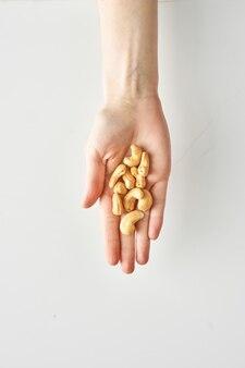 Caloriegedeelte van cashewnoten in de hand van een vrouw