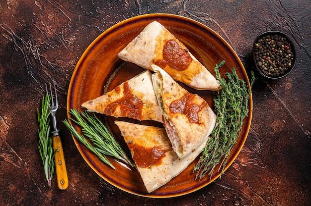 Calzone pizzastukken op rustieke plaat met tomatensaus en kruiden