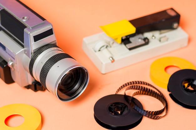 Camcorder met filmstrip op perzik gekleurde achtergrond met filmstrip op perzikkleurige achtergrond