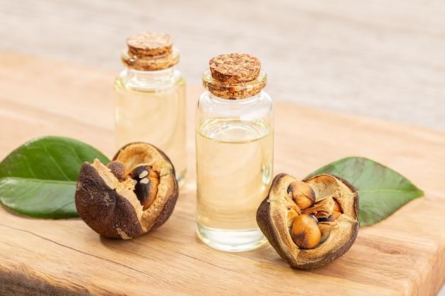 Camelia etherische olie fles en camelia zaden op houten tafel. schoonheid, huidverzorging, wellness