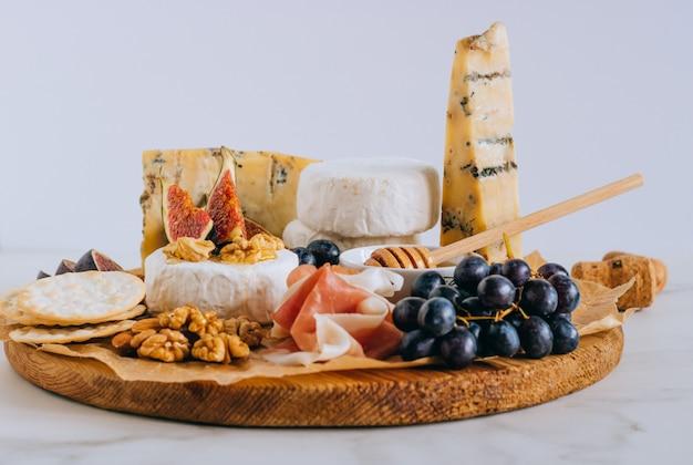 Camembert en blauwe kaas stilton met vijgen, jamon, honing en druiven.