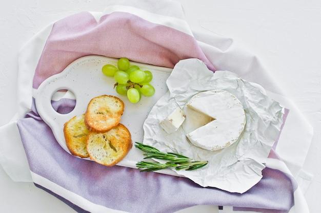 Camembert kaas met noten op een witte snijplank