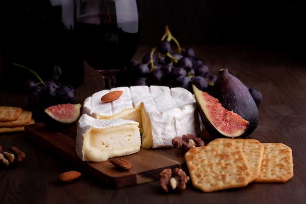 Camembert kaas met wijn, fruit en noten.