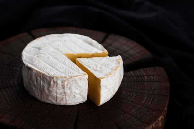 Camembert kaas op zwarte houten tafel, met kopie ruimte. ondiepe scherptediepte