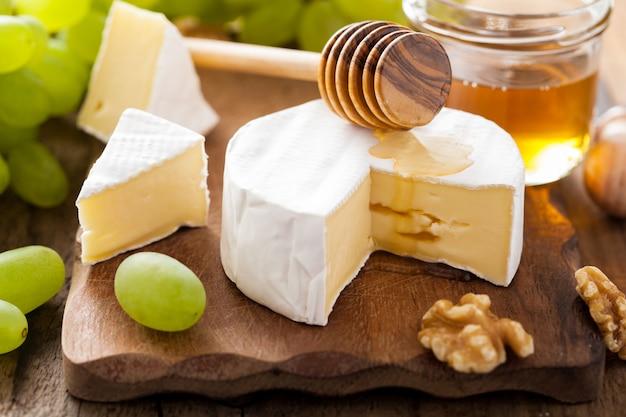 Camembertkaas met druiven, honing en noten op houten achtergrond