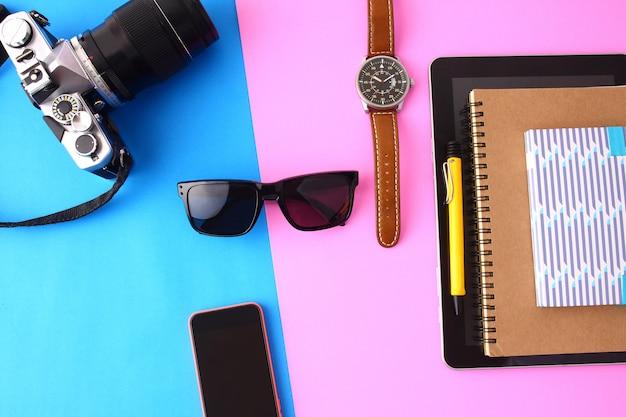 Camera, bril, telefoon, notebook, dagboek op de achtergrond van roze en blauw