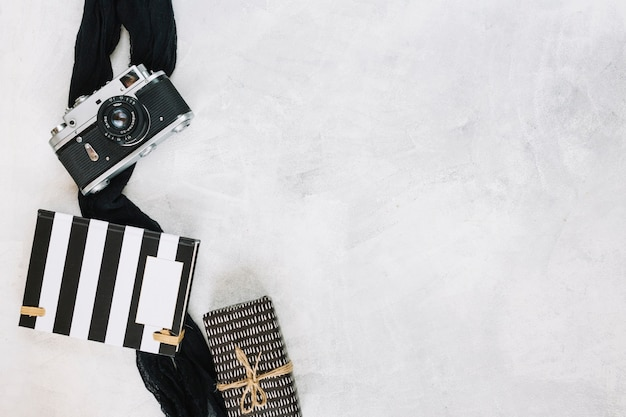 Camera en doek in de buurt van notitieboekje en cadeau