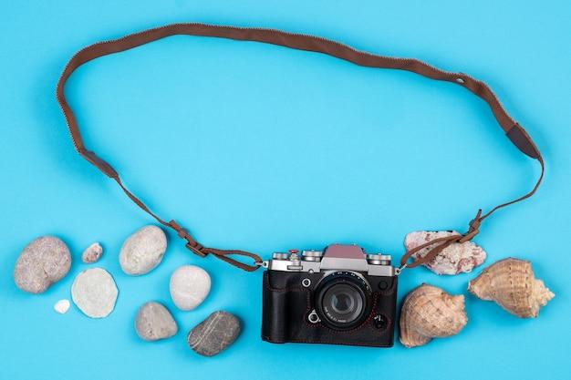 Camera en schelpen op een blauwe achtergrond. achtergrond voor de reiziger