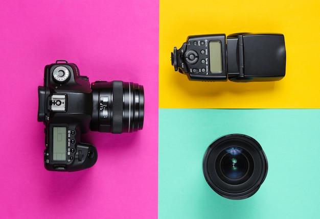 Camera, flitser, lens op een pastel oppervlak.