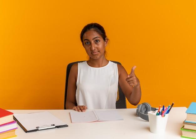 Camera kijken jonge schoolmeisje zit aan bureau met school tools toont u gebaar