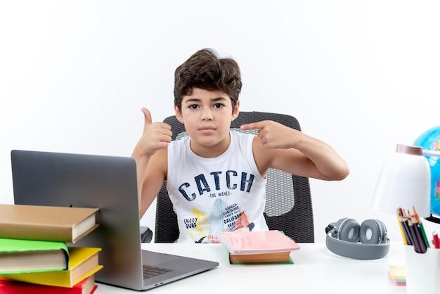 Camera kijken kleine schooljongen zittend aan een bureau met school tools punten aan de zijkant