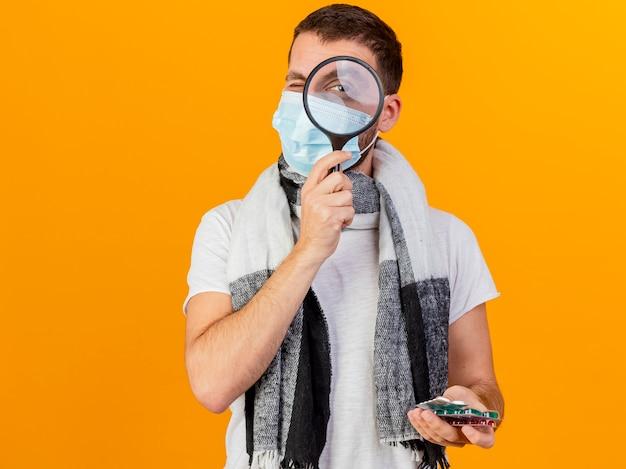 Camera kijken met vergrootglas zieke jongeman met winter hoed bedrijf pillen geïsoleerd op gele achtergrond