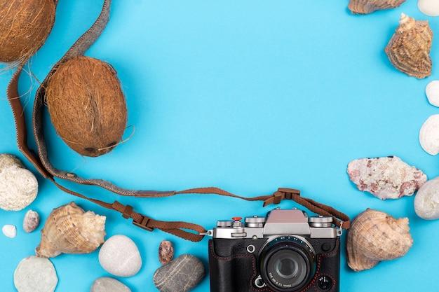 Camera, kokosnoten en schelpen op een blauwe achtergrond. achtergrond voor de reiziger