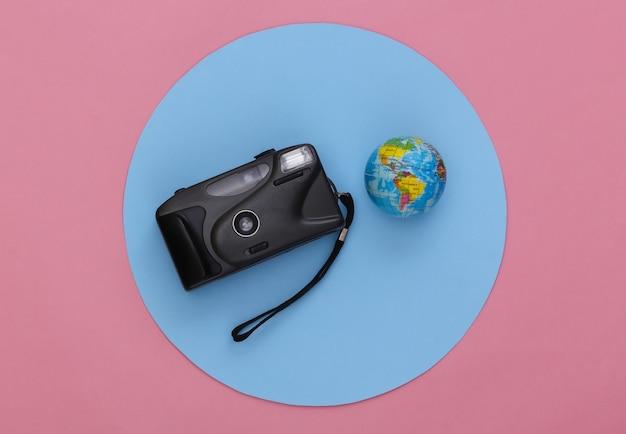 Camera met globe op roze achtergrond met een blauwe cirkel. reisconcept. bovenaanzicht.