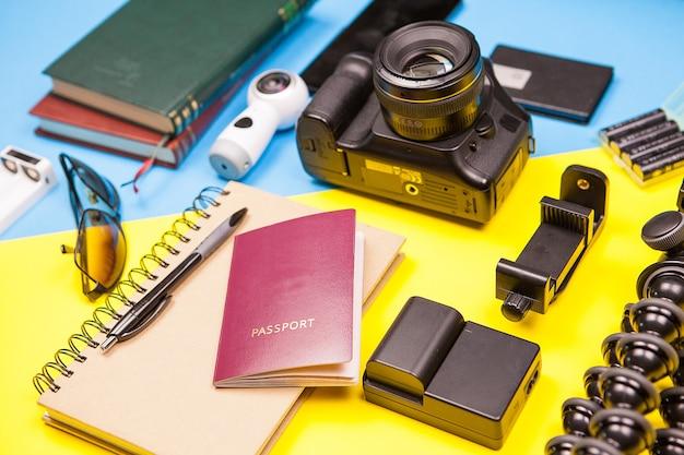 Camera met verschillende accessoires op twee gekleurde achtergrond. reiziger kit