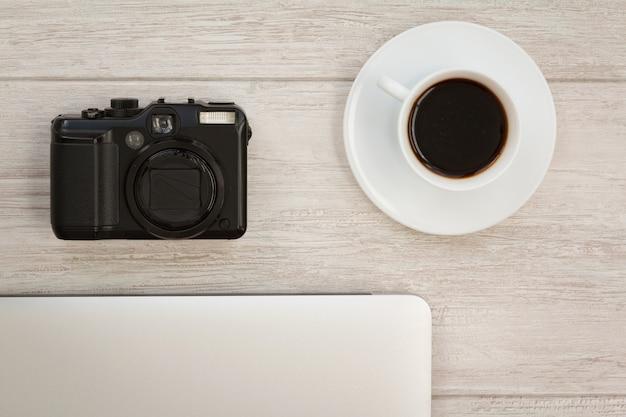 Camera naast een kopje koffie en een laptop