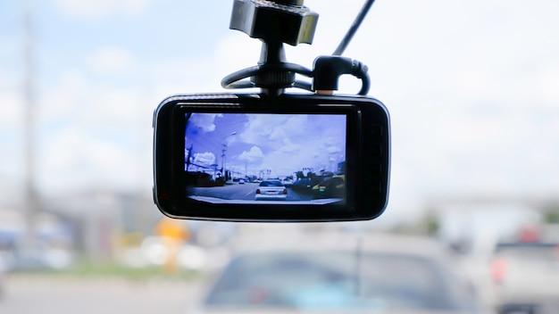 Camera op de voorkant van een auto achtergrond auto's op de weg en wolken in de lucht.