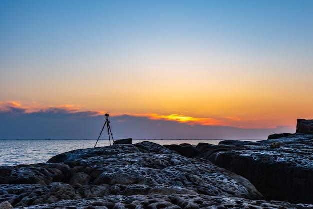 Camera op statief maakt kleurrijke zonsopgang op zee